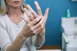 Frau massiert schmerzende Finger wegen Arthritis